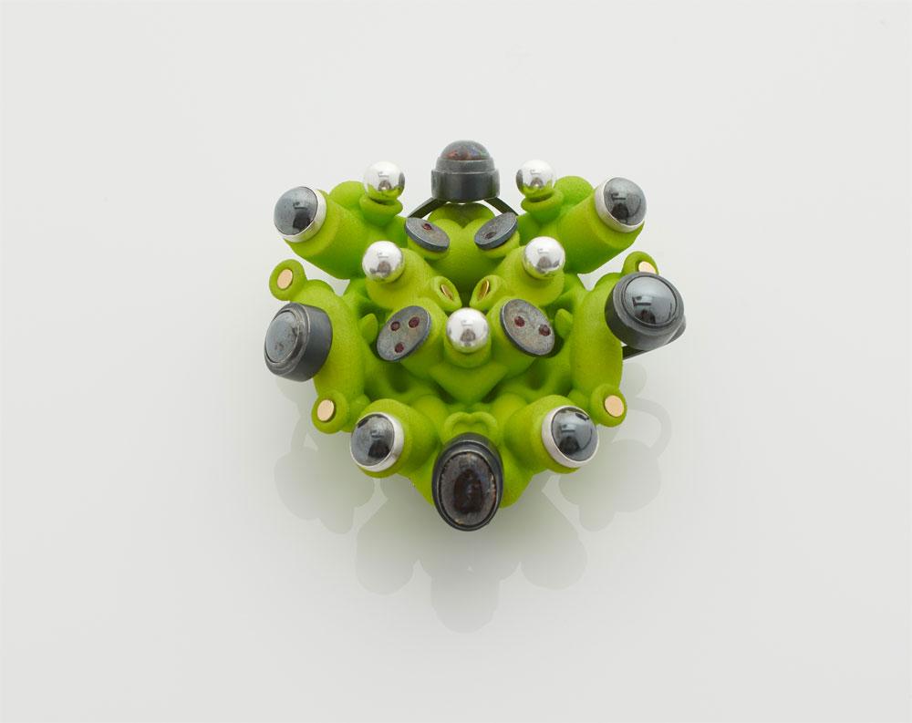 Silvia Weidenbach. Brosche 'ctrl gemGREEN'. 2018. 3D-gedruckter Moondust, Silber, Gold, Opal, Granat. Foto: Sylvain Deleu